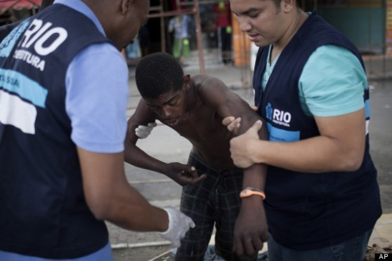 Social workers lead a suspected crack user, who is living in the street, to a van to take him to shelter as part of a program run by Rio de Janeiro's Social Action Secretariat, near the Parque Uniao slum in Rio de Janeiro, Brazil.
